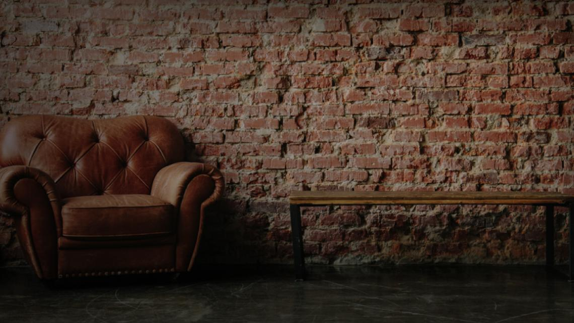 Leather chair and wood table in front of a brick wall